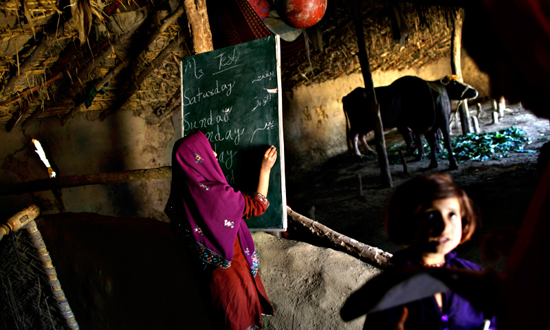 A schoolgirl, center, writes on the blackboard, while her teacher Warda Arshad, 20, right, check the homework of another student during their daily classes in a makeshift school set in a clay house,  part of it is used as a cowshed, in a poor neighborhood on the outskirts of Islamabad.