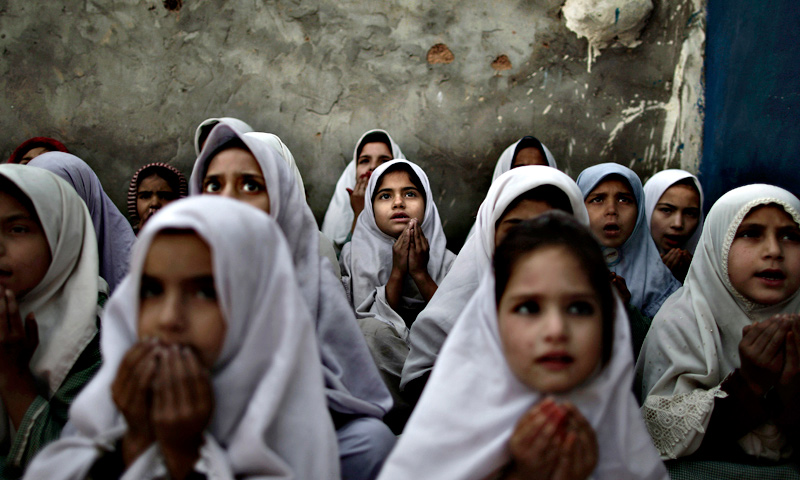 Displaced school girls chant prayers during a class to pay tribute for five female teachers and two aid workers who were killed by gunmen, at a school, on the outskirts of Islamabad.