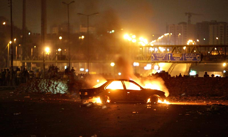 A car allegedly burnt by police and plain-clothed people is seen during clashes in Nasr city area. — Reuters Photo