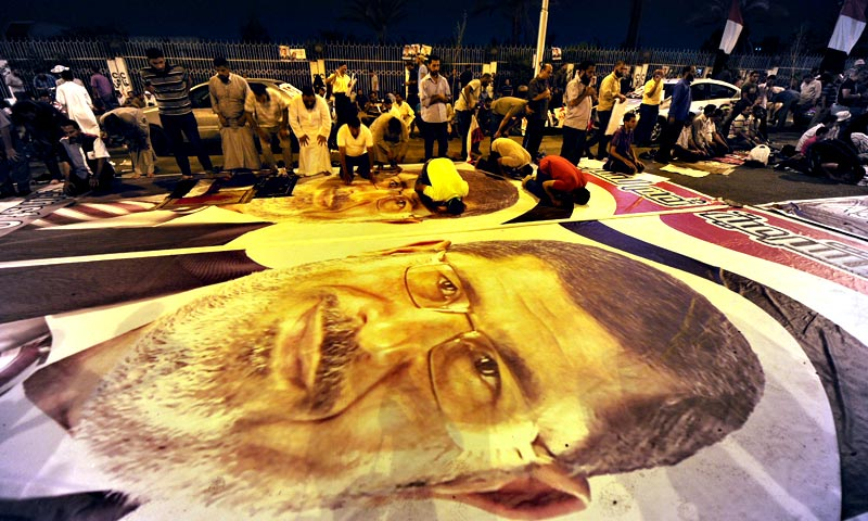 Members of Muslim brotherhood perform prayers on a poster of ousted Egyptian president Mohamed Morsi. — AFP Photo