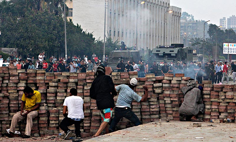 Morsi supporters throw stones from behind a makeshift barricade they built as they take cover from the police. — Reuters Photo