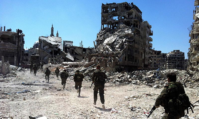 Syrian government forces patrol in the Khalidiyah neighbourhood of the central city of Homs. Government forces bolstered by Lebanese Shia militiamen were poised to retake the largest rebel-held district of Syria's third city Homs, a watchdog and state media said. — AFP Photo