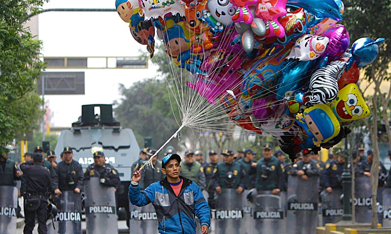 A balloon vendor walks in front of a group of riot police standing guard during an anti-government demonstration that was taking place as Peru's President Ollanta Humala delivered his State of the Nation address, in Lima. — AP Photo