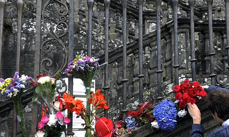 A man displays flowers at the fence of Santiago de Compostela cathedral to honour the victims of a train accident, at Obradoiro square, in the northern Spanish city of Santiago de Compostela.  — AFP Photo