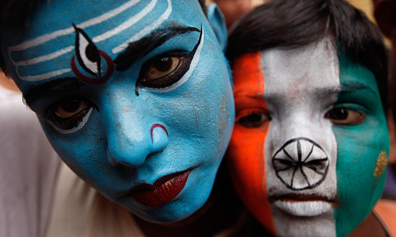 An Indian boy, left, painted with a face of Hindu God Shiva and the other with an Indian flag participate in a walk carrying water from the River Ganges to offer at the Vishwanath Temple in Varanasi. — AP Photo