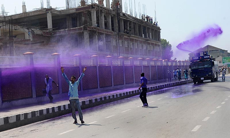 Kashmiri government employees are sprayed with purple-dye water cannon by riot police during a demonstration in Srinagar.  Dozens of government employees were arrested as they tried to stage a protest march in Srinagar demanding a regularisation of contractual jobs and an increase in salary.   — AFP Photo