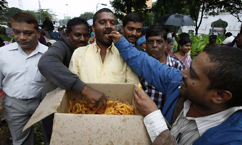 People celebrate by distributing sweets after India's ruling coalition endorsed creating a new state in southern India, in Hyderabad, India, Wednesday, July 31, 2013. — Photo by AP