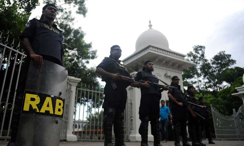 Rapid Action Battalion personnel stand guard in front of the high court in Dhaka on August 1, 2013 after a verdict was delivered in which Bangladesh's Jamaat-i-Islami was banned from contesting next year's elections. — Photo by AFP