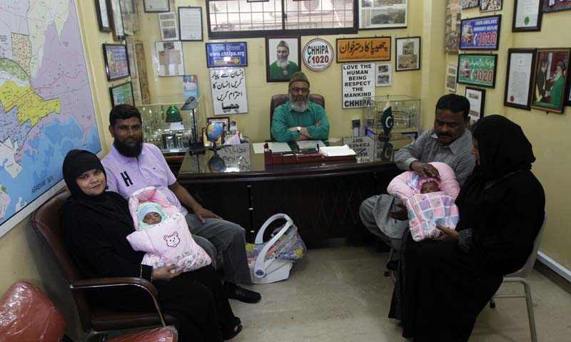 Childless couples sit with newly adopted babies, Fatima (L) and Zainab (R), whom Pakistani television talk show host Aamir Liaquat Hussain gave away on his show, as they pose for photographs at the Chhipa Welfare Association office in Karachi August 1, 2013. — Photo by Reuters