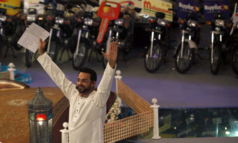 """Aamir Liaquat Hussain, host of the Geo TV channel programme """"Amaan Ramazan"""", gestures while asking participants questions during a live show in Karachi July 26, 2013.   — Photo by Reuters"""
