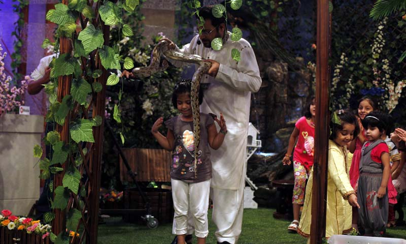 """Aamir Liaquat Hussain, host of the Geo TV channel programme """"Amaan Ramazan"""", puts a snake around a child's shoulders during a live show in Karachi July 26, 2013. — Photo by Reuters"""