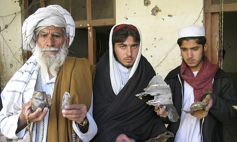 Tribesmen hold pieces of a missile at the site of a missile attack in Mir Ali on the outskirts of Miranshah near the Afghan border.—Photo by AFP