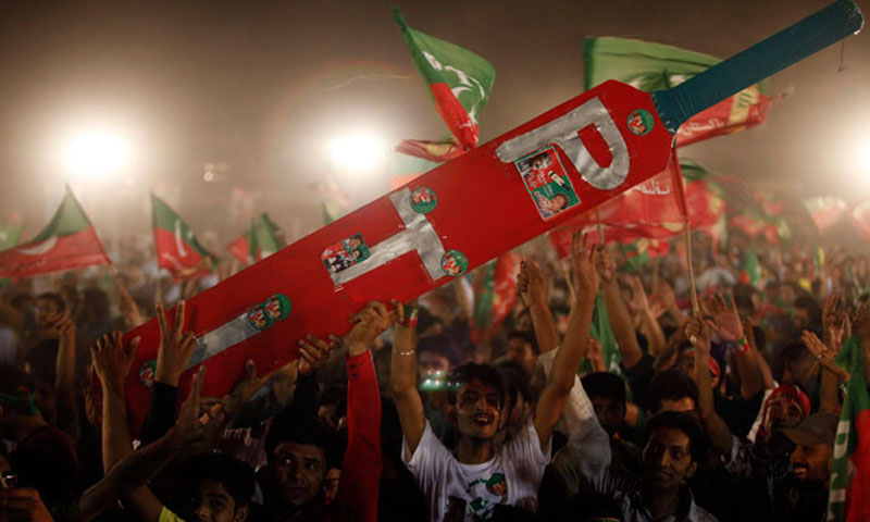 Supporters at a rally carry a giant cricket bat, the symbol of the Pakistan Tehrik-i-Insaf (PTI) party.—File Photo