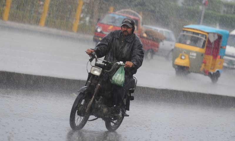 A commuter rides his motorbike on a rainy day in the streets of in Karachi. — AFP