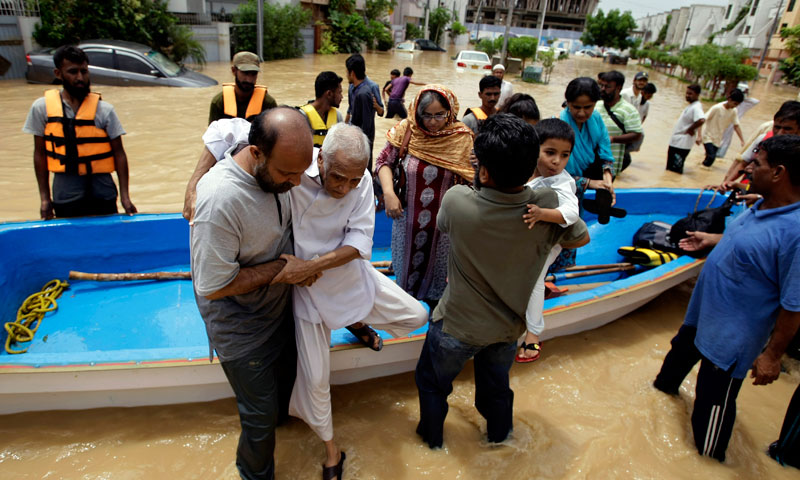 People get off from a boat after rescued by soldiers from a flooded area caused by heavy rains on the outskirts of Karachi, Sunday, Aug. 4. – Photo by AP