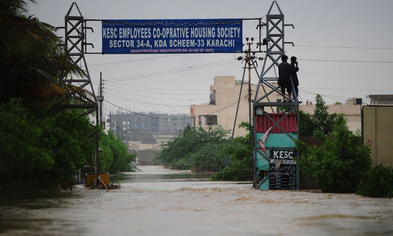 Residents stand on an electricity pylon in a flooded area in Karachi on August 4. – Photo by AFP