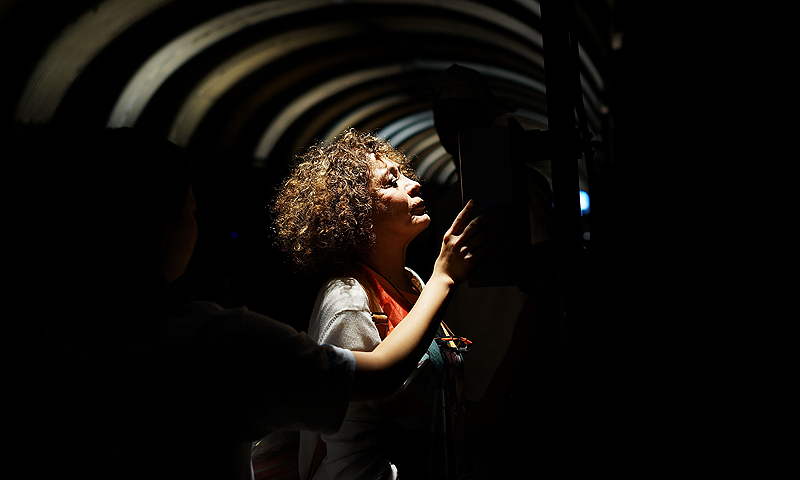 A woman speaks into a silver intercom as part in the Park Avenue Tunnel after it has been temporarily transformed into an art exhibition for pedestrians on August 3, 2013 in New York City. — AFP Photo
