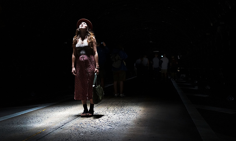 A woman pauses under a light inside the Park Avenue Tunnel after it has been temporarily transformed into an art exhibition for pedestrians on August 3, 2013 in New York City.  — AFP Photo