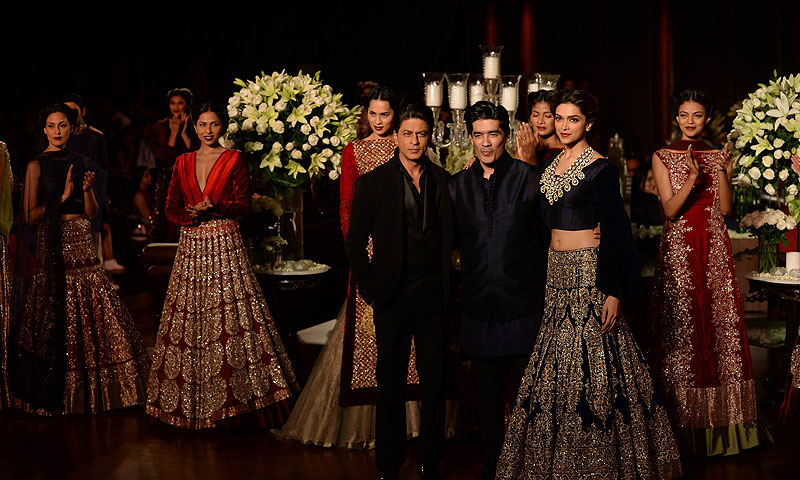 Actor Shah Rukh Khan (L), Indian fashion designer Manish Malhotra (C) and Indian Bollywood actress Deepika Padukone (R) pose during the Grand Finale of PCJ Delhi Couture Week 2013 in New Delhi.—Photo by AFP