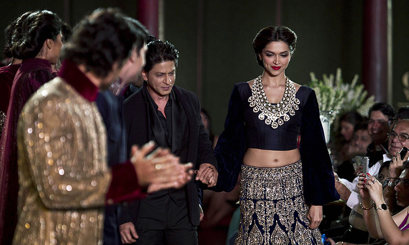 Actors Sharuk Khan second left and Deepika Padukone walk on the ramp to displays Indian designer Manish Malhotra