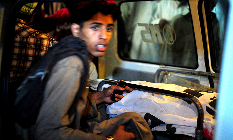 A boy sits next to the body of a blast victim in an ambulance in Karachi. Most of those killed in the Lyari blast  were aged from six to 15 years old. -Photo by AFP