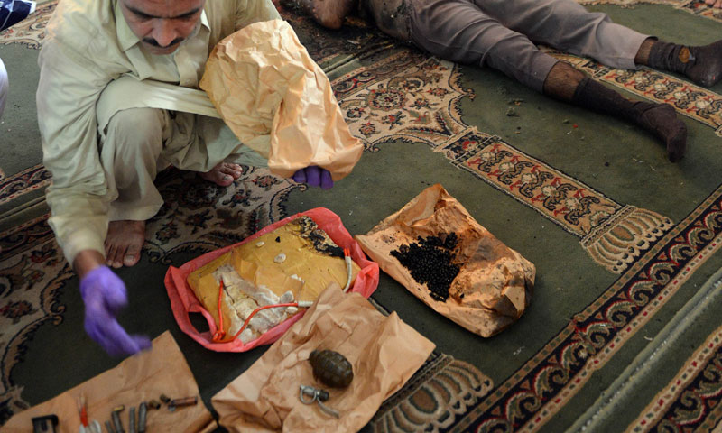 A police official displays explosives next to the body of the suicide bomber at the mosque on the outskirts of Islamabad on August 9, 2013.—AFP Photo