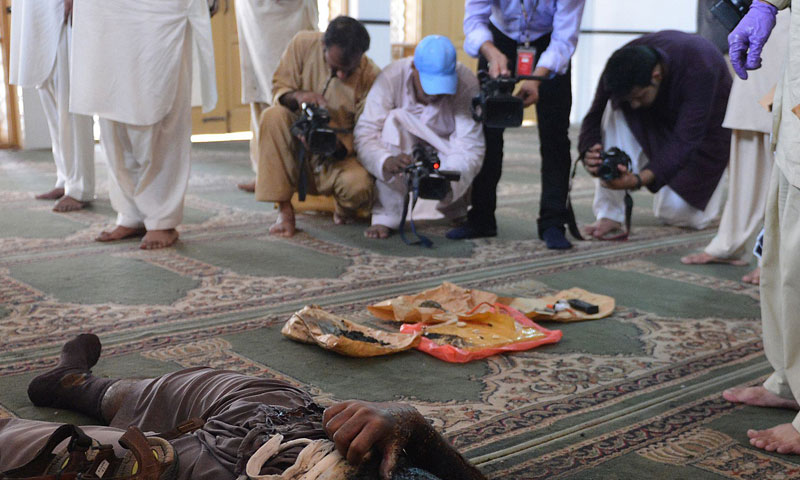 Television cameramen record footage of explosives and the body of the suicide bomber inside the mosque on the outskirts of Islamabad on August 9, 2013.—AFP Photo