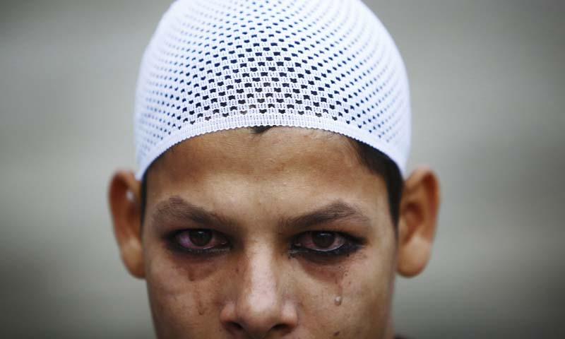 Tears roll from the eyes of a Muslim boy after he applied kohl to his eyelid before Eid ul-Fitr mass prayers at the Kashmiri Takiya Jame mosque in Kathmandu August 9, 2013. — Photo Reuters