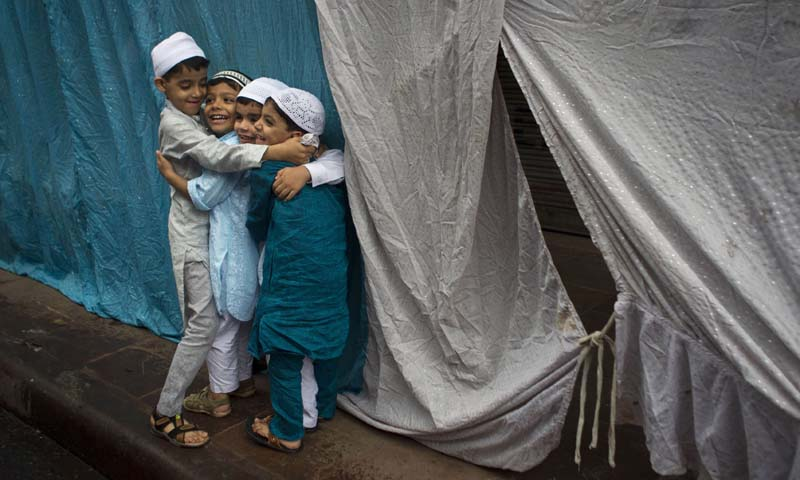 Indian Muslim children hug and wish each other after offering Eid prayers in New Delhi, India, Friday, Aug. 9. — Photo AP
