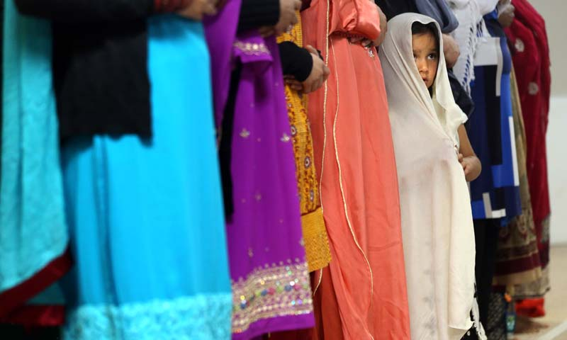 A little girl stands by a family member during a service to celebrate Eid ul-Fitr, the three-day holiday marking the end of Ramadan, Thursday, August 8, 2013, at the Tri-State Islamic Center in Dubuque, Iowa. — Photo AP