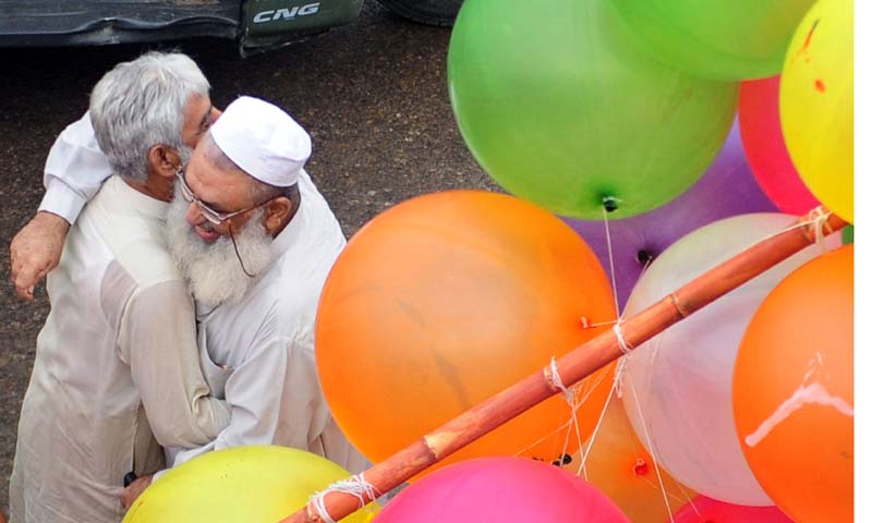 Pakistani Muslims exchange greetings after offering Eid ul-Fitr prayers during the first day of their religious festival in Karachi on August 9, 2013. — Photo AFP