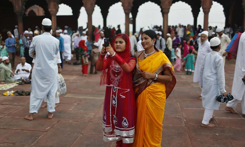 A Muslim woman takes pictures with her mobile phone at the Jama Masjid (Grand Mosque) during Eid u-Fitr in the old quarters of Delhi August 9, 2013. — Photo Reuters