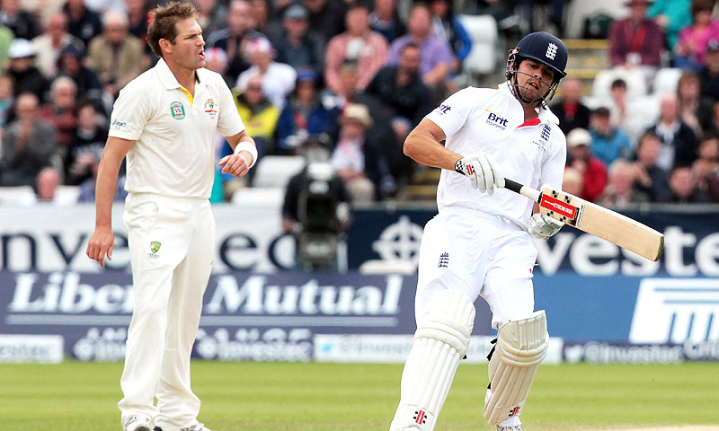 Australia's Ryan Harris (L) looks-on as England captain Alistair Cook (R) completes a run. -Photo by AFP