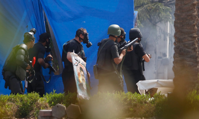 Riot police are seen clashing with protestors, at Rabaa Adawiya square, where they are camping, in Cairo.