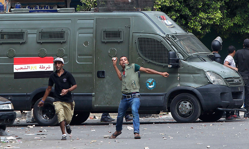 A local resident throws stones towards pro-Morsi protestors.