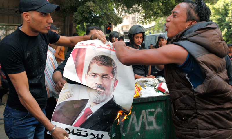 Local residents burn a poster of ousted President Morsi, which was taken after his supporters fled.