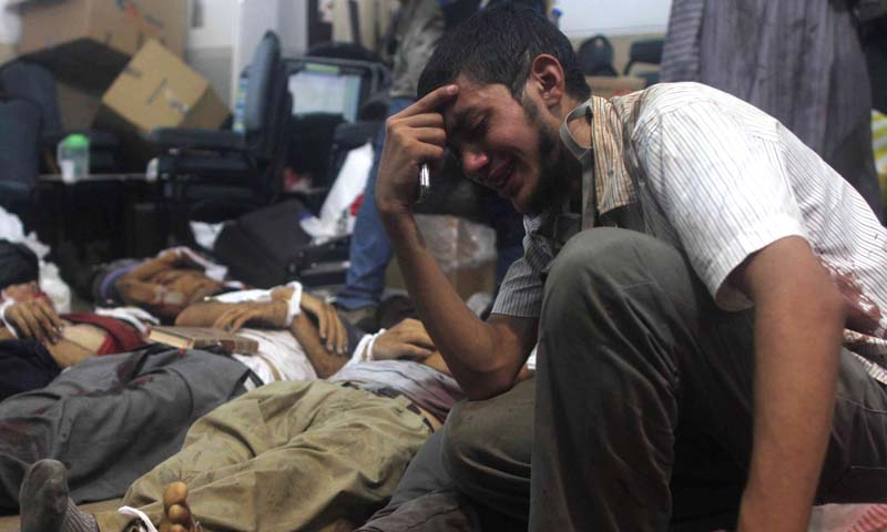 A man grieves as he looks at one of many bodies laid out in a make shift morgue after Egyptian security forces stormed two huge protest camps at the Rabaa al-Adawiya and Al-Nahda squares where supporters of ousted president Mohamed Morsi were camped,  in Cairo, on August 14, 2013. — Photo AFP