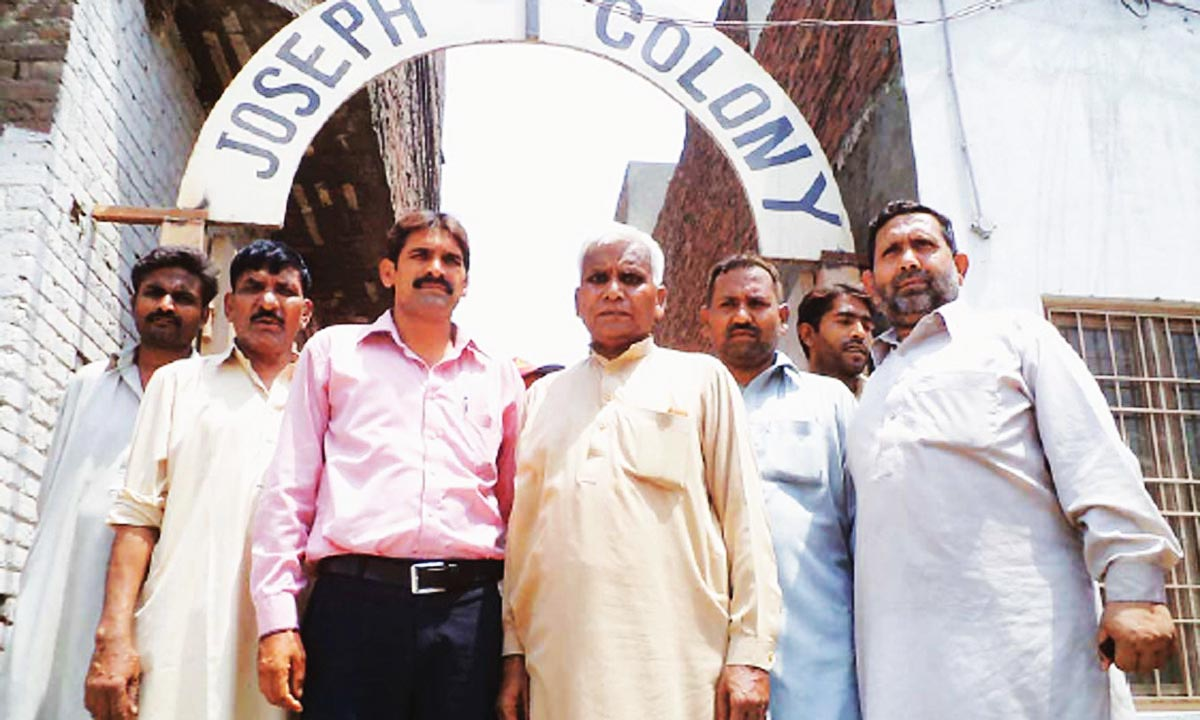 Martin Javed Michael (fourth from right) stands at the entrance of Joseph Colony. -Photo by Mohammad Usman