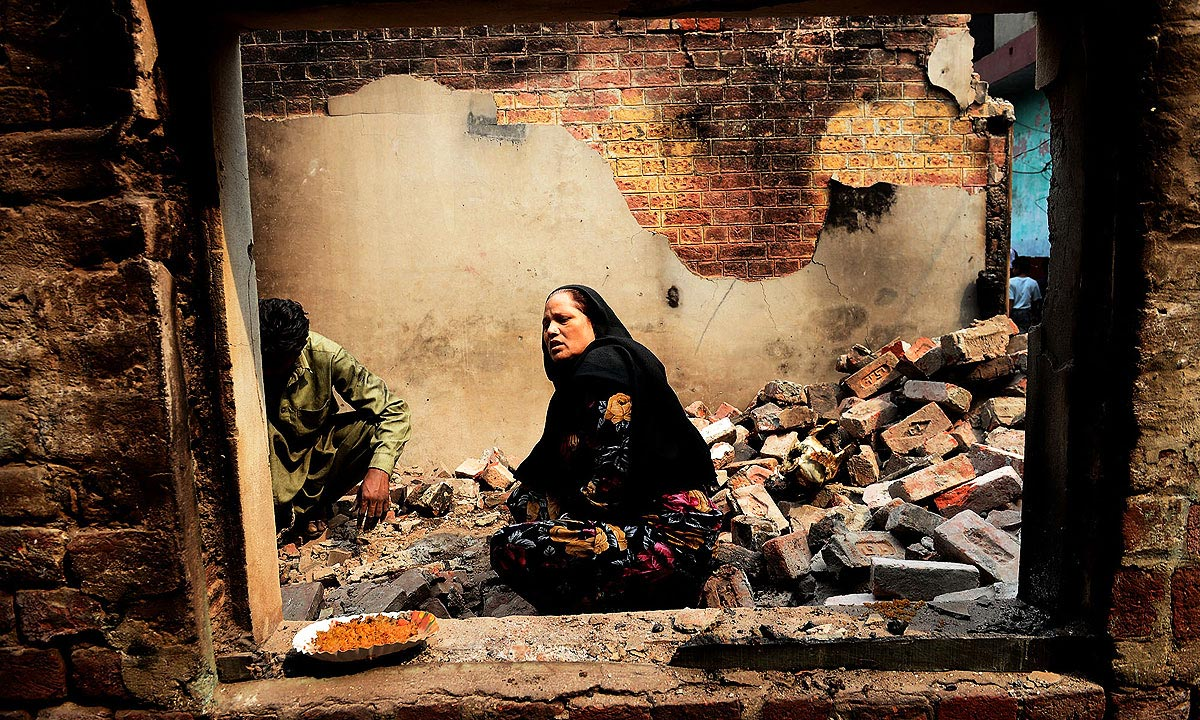 A woman sits inside her burnt house in Joseph Colony | Arif Ali, White Star
