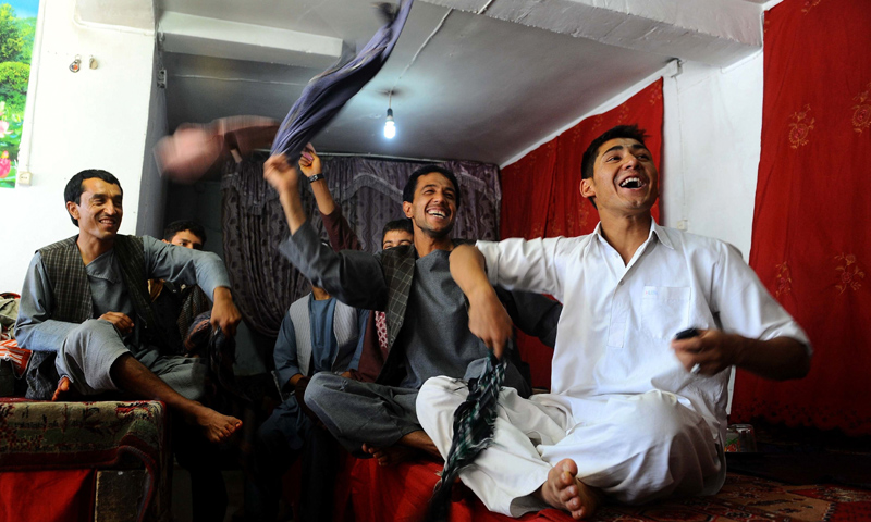 Afghan fans watch the football match between Afghanistan and Pakistan  on a TV screen in Herat. -Photo by AFP