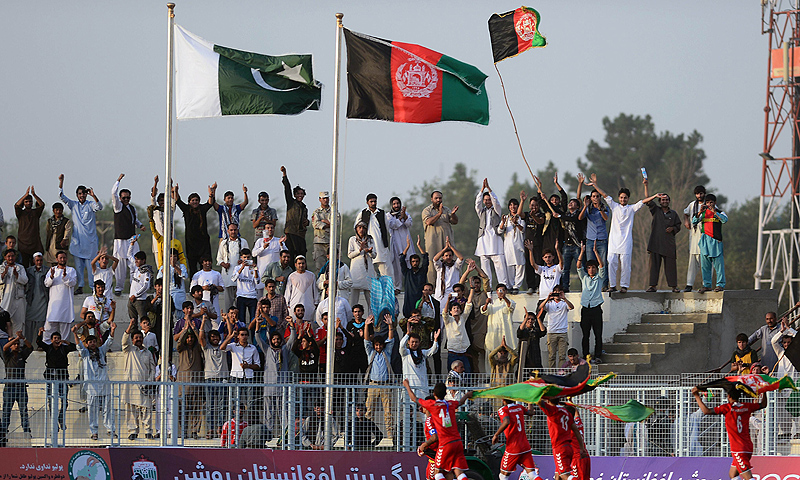 Spectators react in the stands as Afghan footballers celebrate their 3-0 win against Pakistan. -Photo by AFP