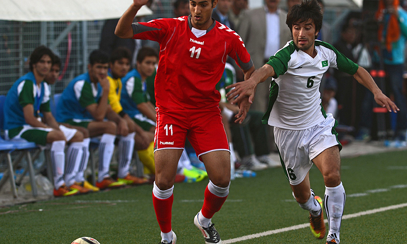 Afghan (in red) and Pakistani football players tussle for the ball. -Photo by AFP
