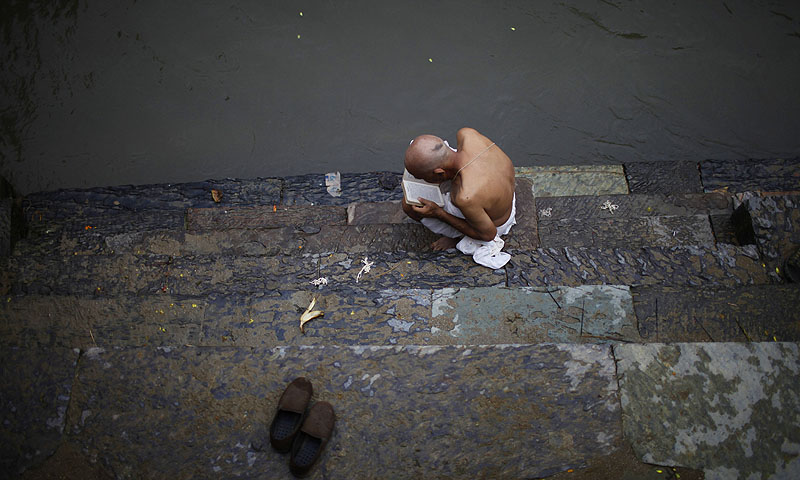 A Hindu devotee reads holy scripts during Janai Purnima.—Photo by AP
