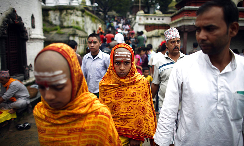 Young Nepalese Hindu priests, covered in yellow robes, walk during Janai Purnima.—Photo by AP
