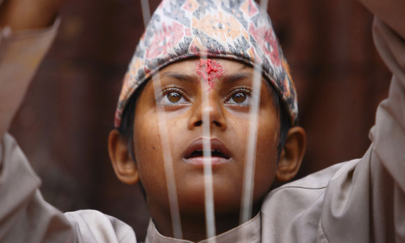 A young Hindu priest arranges sacred thread during the Janai Purnima.—Photo by Reuters