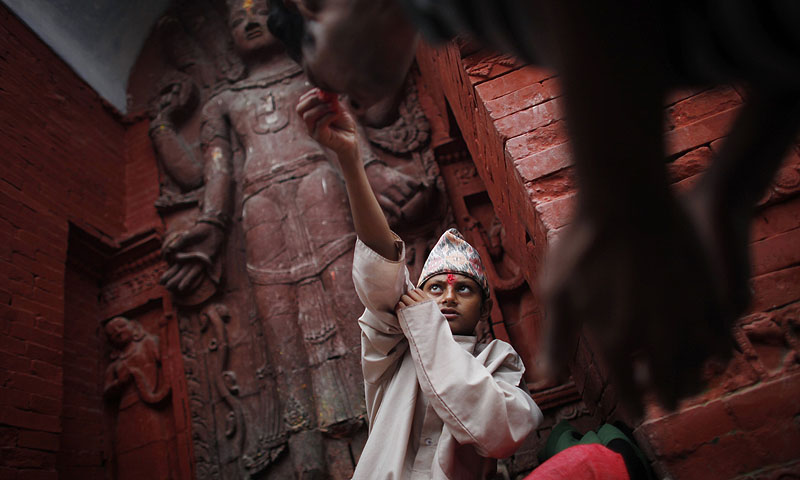 A young Nepalese Hindu priest offers vermillion mixed with rice to a devotees during Janai Purnima.—Photo by AP