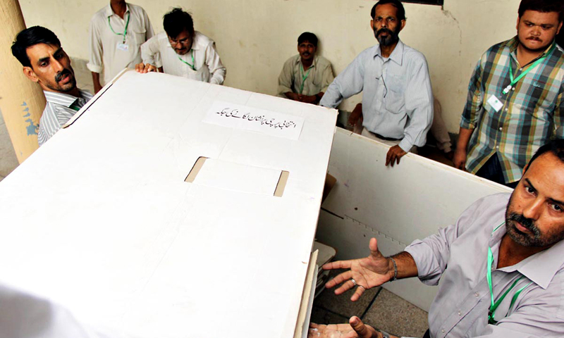 Workers of Election Commission shifting polling items for by-elections in the port city. — Online Photo