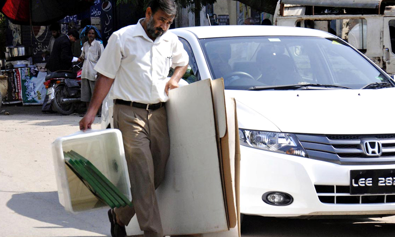 Worker of election commission shifts ballot boxes and other polling items for by-elections, at session court in the provincial capital. — Online Photo