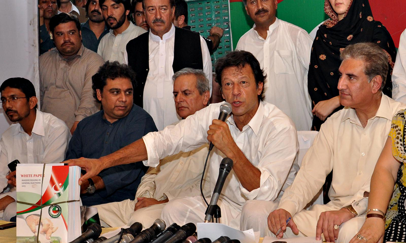 Chairman Pakistan Tehreek-e-Insaaf Imran Khan flanked by Deputy Parliamentary Leader of Pakistan Tehrik-e-Insaf (PTI) in National Assembly & party's Vice Chairperson Shah Mehmood Qureshi & Pakistan Threek-e-Insaf President Makhdoom Javed Hashmi talking to media persons during unveil a white paper consisting of 2000 pages over alleged rigging in the general elections 2013, at PTI Central Secretariat. — Photo by INP