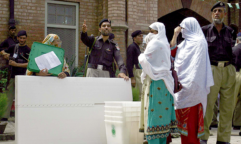 Presiding officials carry electoral material under the  supervision of security forces for By-Elections 2013 at Government School No. 01 in Peshawar. — Photo by PPI